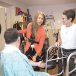 Julia Chevan (right) leads Associate Professor of Physical Therapy Angela Abeyta Campbell through an exercise in the simulation lab at Springfield College.